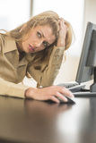 Tired Businesswoman Looking Away While Sitting At Computer Desk Royalty Free Stock Images