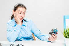 Tired businesswoman looks at the alarm clock and waits Royalty Free Stock Photography