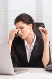 Tired businesswoman. Tired middle-aged businesswoman sitting at her working and keeping her eyes closed Stock Photography