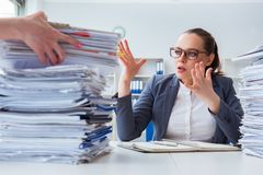 The tired businesswoman with paperwork workload. Tired businesswoman with paperwork workload Stock Photo