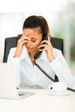 Tired businesswoman phone. Tired businesswoman using landline phone in office Stock Images