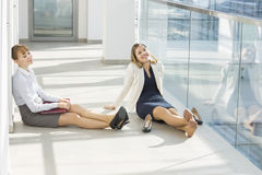 Tired businesswoman relaxing at office hallway Royalty Free Stock Photography