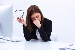 Tired businesswoman rubbing her eyes. In office Royalty Free Stock Photo