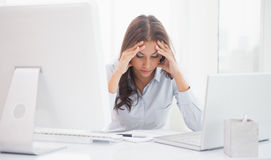 Tired businesswoman sitting at her desk Stock Photo