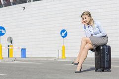 Tired businesswoman sitting on luggage Royalty Free Stock Images