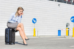 Tired businesswoman sitting on luggage Royalty Free Stock Image