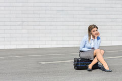 Tired businesswoman sitting on luggage Royalty Free Stock Photography