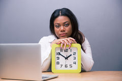 Tired businesswoman sitting at the table with clock Stock Photography