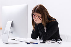 Tired businesswoman sitting at the table and covering her face Royalty Free Stock Photos
