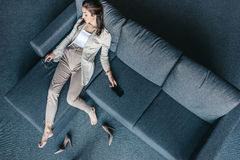 Tired businesswoman sleeping on couch after hard working day. Overhead view of tired businesswoman sleeping on couch after hard working day Stock Photos