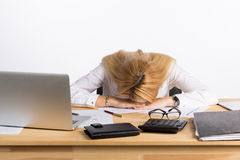 Tired businesswoman sleeping on the desk. In front of the computer screen Stock Image