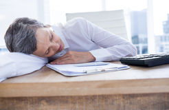 Tired businesswoman sleeping at her desk Stock Photos