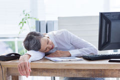 Tired businesswoman sleeping at her desk. In her office Royalty Free Stock Photo
