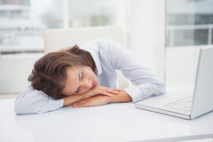 Tired businesswoman sleeping at her desk. In her office Royalty Free Stock Image