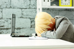 Tired businesswoman sleeping on her workplace Royalty Free Stock Photography
