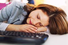 Tired businesswoman sleeping at office. Holding her head on the desk Stock Image