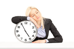 Tired businesswoman sleeping on a wall clock at workplace Royalty Free Stock Photo