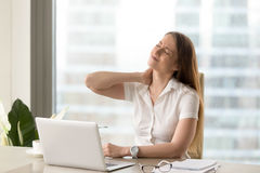 Tired businesswoman suffering of office syndrome. Businesswoman feeling pain in neck after sitting at the table with laptop. Tired female suffering of office Royalty Free Stock Photo