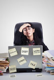 Tired businesswoman thinking in office. Portrait of a tired young businesswoman thinking her problems in the office while holding her forehead Royalty Free Stock Photography
