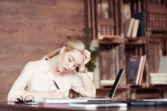 Tired businesswoman using laptop and taking notes Stock Photos