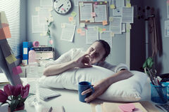 Tired businesswoman waking up in office royalty free stock images