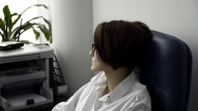 Tired businesswoman in white shirt sitting in blue leather office chair, sighing, and looking out the window in a modern stock photos