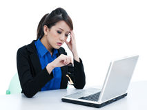 Tired businesswoman at work. Portrait of a tired young businesswoman with laptop and her hand on head over white background Royalty Free Stock Photos