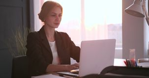 Tired businesswoman working on laptop at office stock video