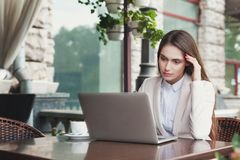 Young businesswoman outdoors working with laptop. Tired businesswoman working with laptop sitting at summer terrace cafe. Lifestyle portrait of young business Stock Photo