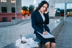 Tired businesswoman works, financial statements. Tired businesswoman works outdoor, financial statements, business center on background. Modern building Royalty Free Stock Photo