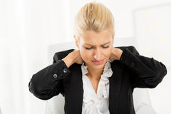Tired Businesswoman. Young tired businesswoman holding hands on the neck with a pained expression on her face Stock Photo