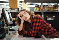 Tired cashier lady lies on workspace in supermarket shop. Picture of tired cashier lady lies on workspace in supermarket shop. Looking aside Stock Photography