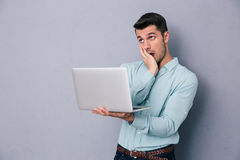 Tired casual man standing with laptop Stock Photography