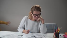 Tired Caucasian woman in eyeglasses sitting at the table and reading as two cheerful children running around. Beautiful