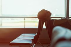 Tired caucasian woman sleeping in airport lounge waiting for flight. Tired caucasian woman sleeping in airport lounge. Transit passenger waiting for flight royalty free stock photo