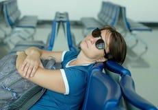Tired caucasian woman sleeping in airport lounge waiting for flight. Tired caucasian woman sleeping in airport lounge. Transit passenger waiting for flight stock photo