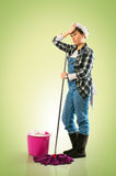 Tired Charwoman. Woman with mop and bucket tired of cleaning the floor on green background stock photos