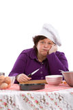 Tired chef. Mature woman leaning on her hand very tired after cooking Stock Images