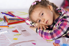 A tired child - an artist with a sketch. And colored pencils in a checkered shirt on a white background Royalty Free Stock Photography