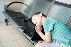 Tired child boy sleeping at the airport. Canceled flight stock photography