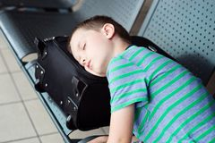 Tired child boy sleeping at the airport. Canceled flight stock image