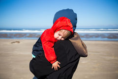 Tired Child at Coast. A very sleep kid rests in the arms of his grandmother after playing at the beach in the Pacific northwest Royalty Free Stock Photo