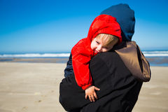Tired Child at Coast. A very sleep kid rests in the arms of his grandmother after playing at the beach in the Pacific northwest Royalty Free Stock Images