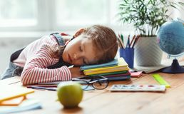 Tired child girl fell asleep when she did her homework  at home. Tired child girl fell asleep when she did her homework, studied writing and reading  at home royalty free stock image