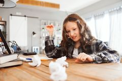 Tired child girl throwing homework with mistakes. royalty free stock image