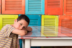 Tired child resting on table royalty free stock photography