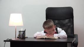 Tired child sitting at desk and sleeping with head on book, funny portrait, little pupil and big eyeglasses, lost childhood. UHD 4K stock video footage