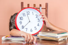 Tired child sleeping and holding a clock Stock Image