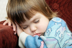 Tired child sleeping portrait on chair close up Royalty Free Stock Image