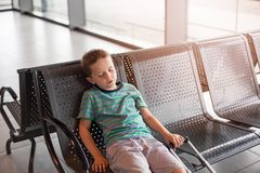 Tired child sleeping in waiting room for passengers. Stock Photography